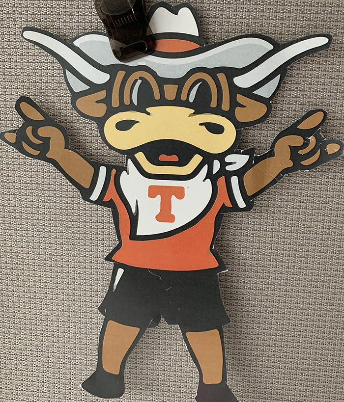 "An image of a piece of team paraphernalia from the University of Texas Longhorns. A cartoon representation of the UT mascot wears a cowboy hat and flashes the ""Hook 'em Horns"" sign with his suspiciously human-looking hands."