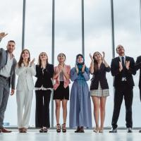 group of people dressed in business clothing applauding