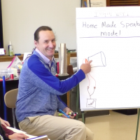 teacher chris newlan shows student diagram for making a home made speaker
