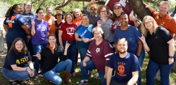 Members of the Dana Center staff gather together wearing shirts representing their various collegiate backgrounds.