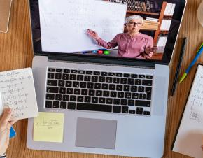 A high-angle view of a student's laptop on a desk covered in notes. On the screen, an instructor tecahes mathematics.