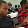 Several college-aged students work together in a mathematics classroom.